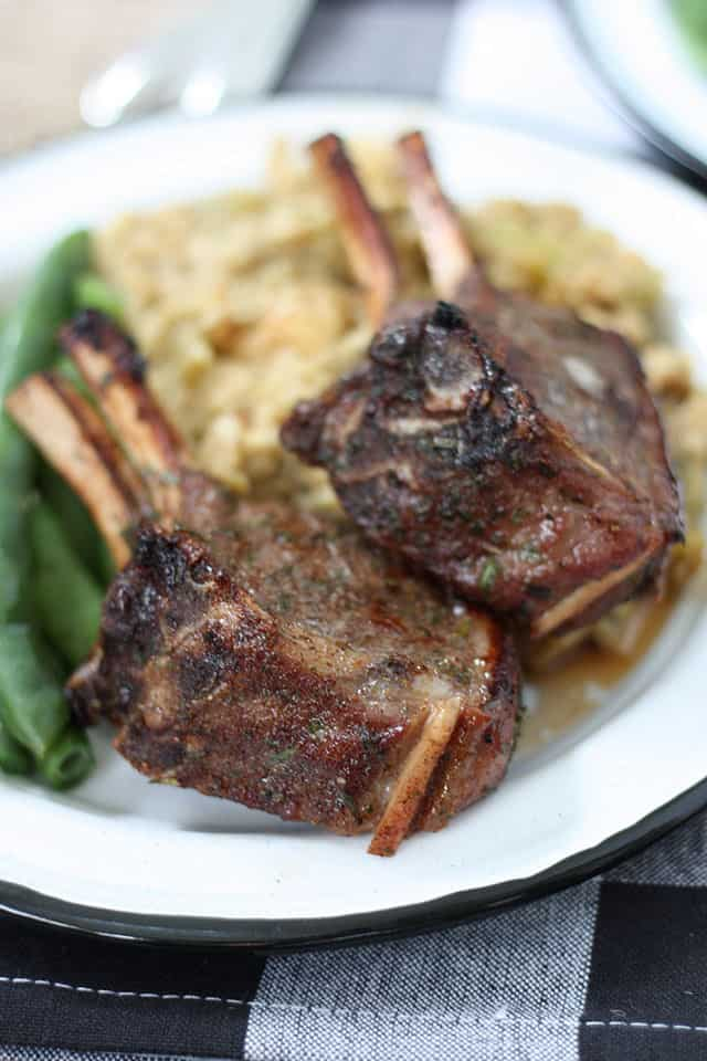 Close up shot of two baked lamb chops with green beans and stuffing