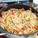 spicy shrimp pasta in a skillet with Parmesan cheese being sprinkled