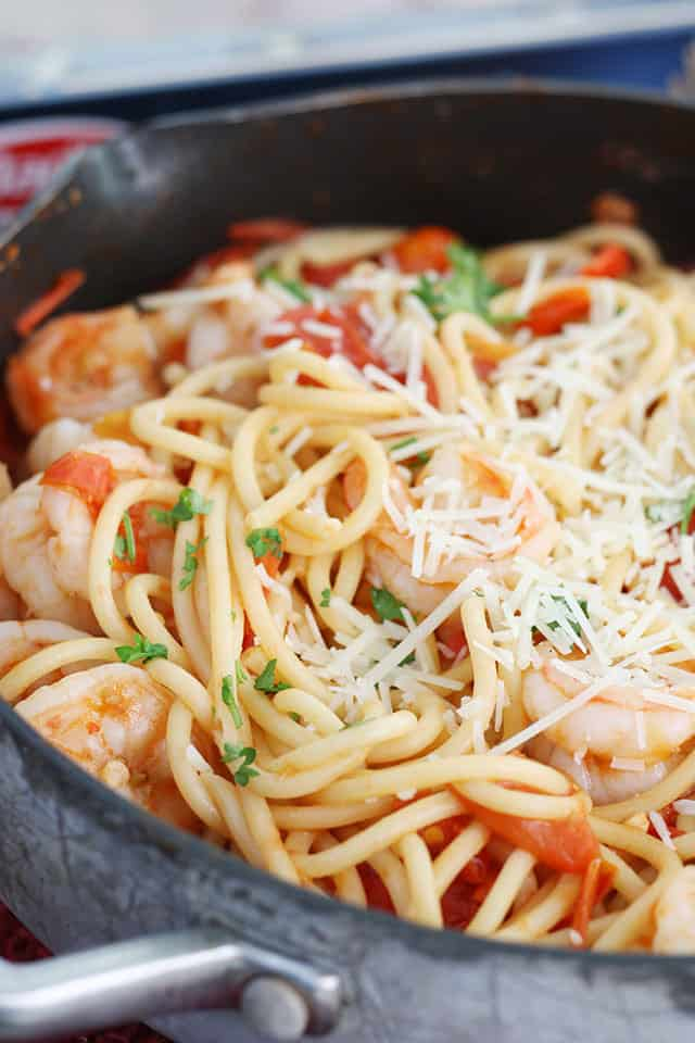 A close up of spicy shrimp pasta in a skillet topped with Parmesan cheese