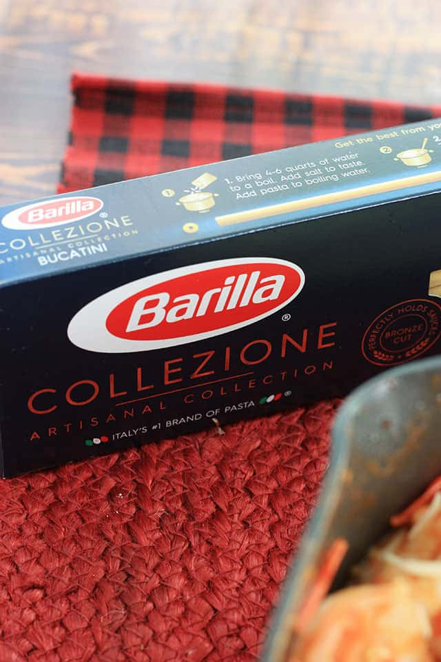 A box of bucatini pasta on a red placemat