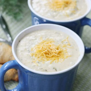 Two soup mugs full of cream of broccoli soup