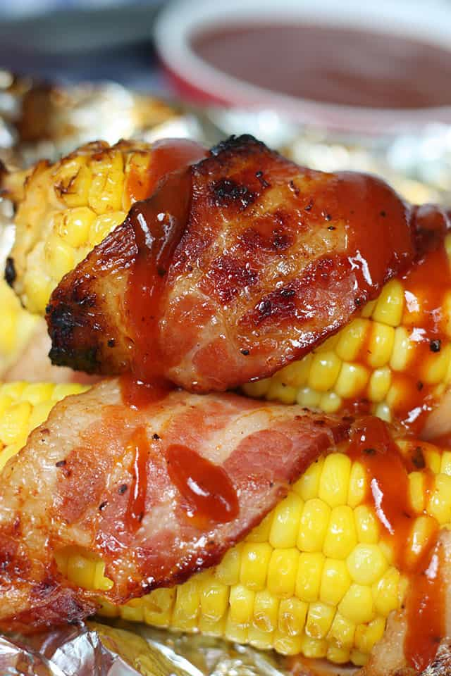 Bacon wrapped around ears of corn and drizzled with BBQ sauce