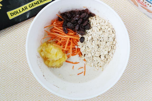 Adding grated carrot, oats, raisins, and pineapple to a white mixing bowl