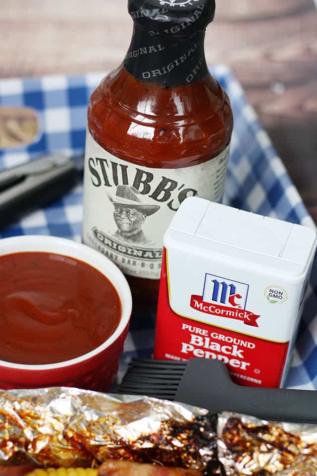 Stubb's BBQ sauce and McCormick Black pepper on a tray in front of grilled corn