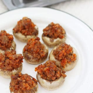 Sausage stuffed mushrooms on a white serving platter