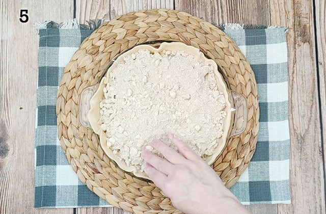 Spreading the crumb topping evenly over the pie