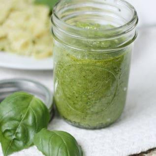 Spinach pesto in a mason jar next to fresh basil leaves