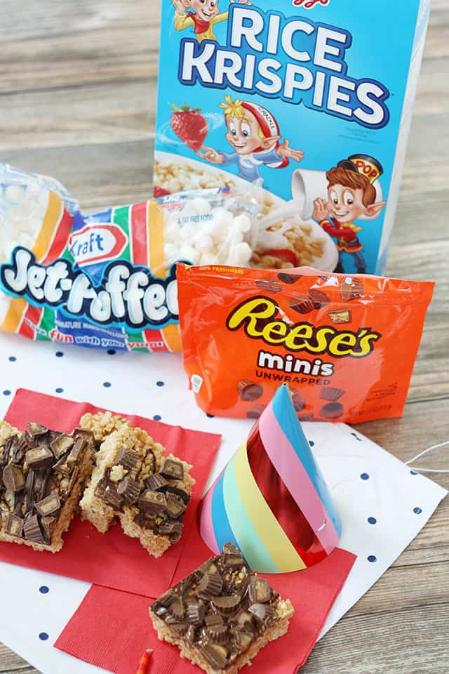 Peanut butter rice krispie treats in front of cereal box, reese cups, and marshmallows