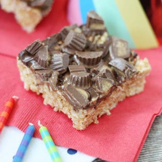 Reese cup rice krispie treat square on a red napkin with birthday candles in front