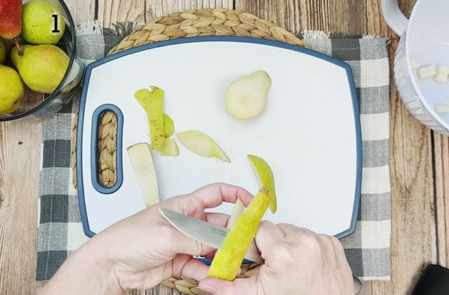 Peeling and chopping pears for pear pie on a white cutting board