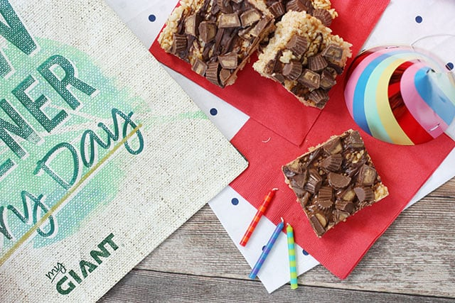 Peanut butter cup rice krispie treats on a red napkin next to a reusable shopping bag