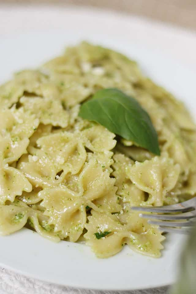 Bowtie pasta mixed with pesto and topped with a basil leaf
