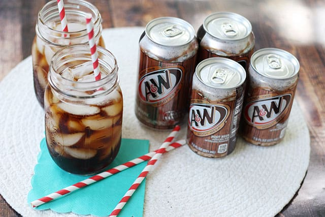 Glasses of ice and root beer next to root beer cans