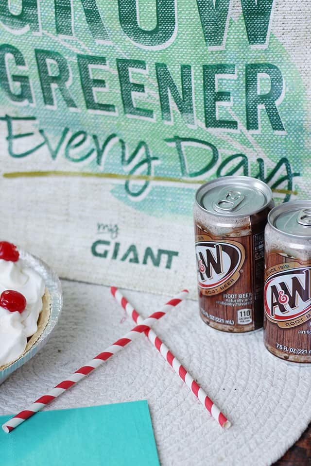 A reusable shopping bag with cans of root beer in front