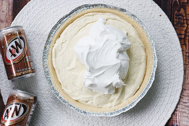 Spreading whipped topping on root beer float pie