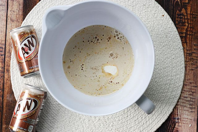 Vanilla pudding mix, root beer, and milk in a white mixing bowl
