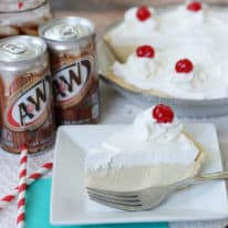 A slice of root beer float pie on a white plate with cans of root beer in the background