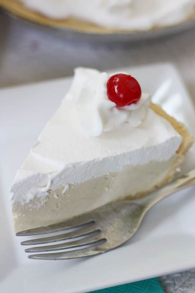 A slice of root beer float pie on a white plate with a fork
