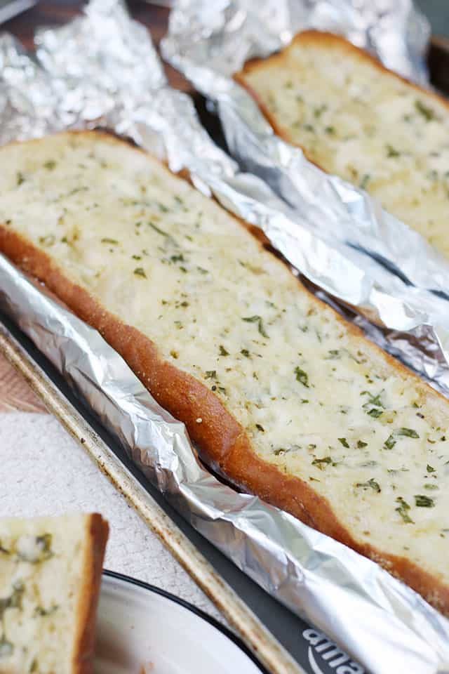 Loaves of garlic bread on foil on top of a baking sheet