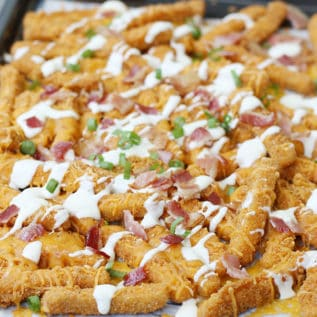 Loaded ranch chicken fries on a parchment lined baking sheet