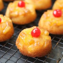 A pineapple upside down cupcake on a wire rack on a cookie sheet