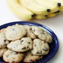 Banana chocolate chip cookies on a blue plate with bananas in the background