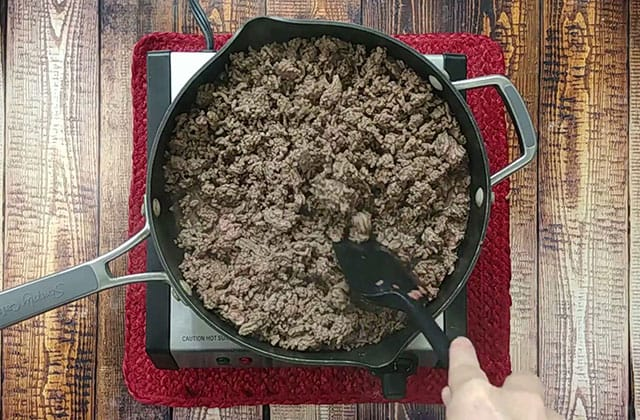 Cooking ground beef in a skillet with a spatula