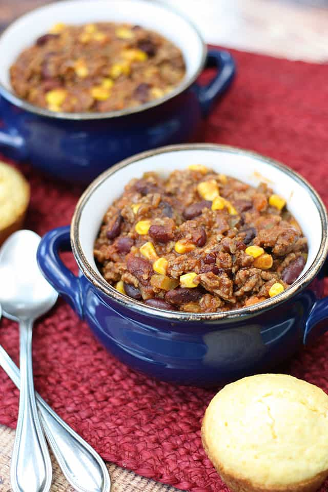 Two blue bowls of crockpot chili next to a cornbread muffin
