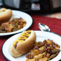 Crockpot baked beans on white plates next to hot dogs