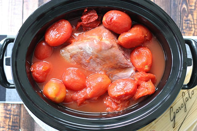 Beef roast and canned whole tomatoes in a slow cooker
