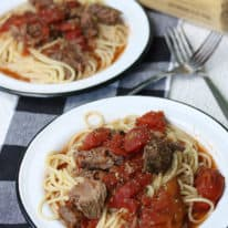 Slow cooker braised beef over bucatini pasta on two small white plates