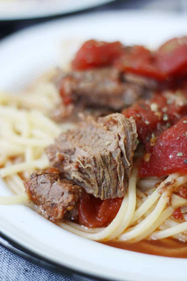 Pieces of braised beef and tomatoes over pasta on a white plate