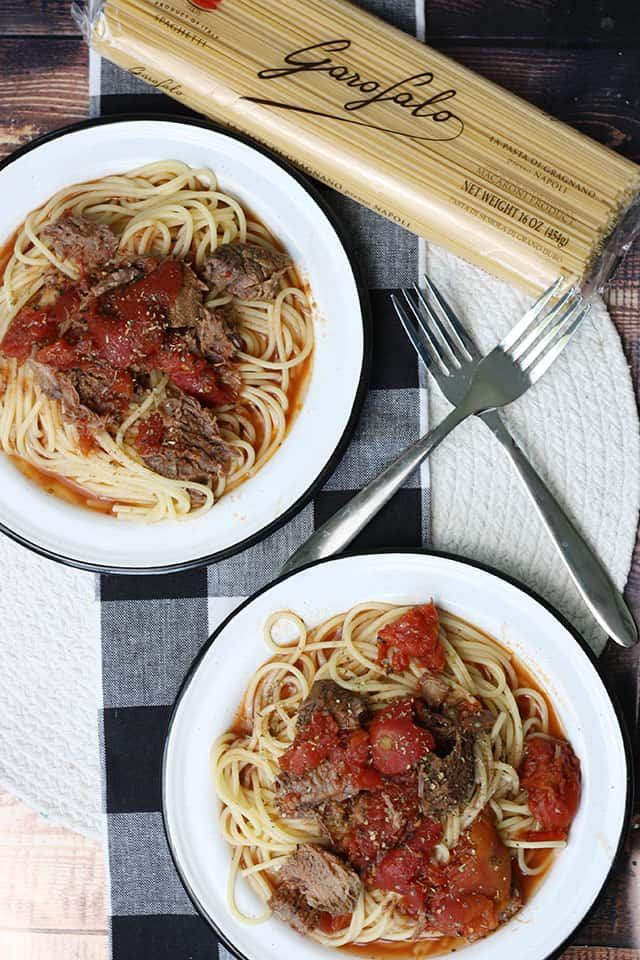 An overhead picture of two plates of braised beef pasta on a black plaid placemat
