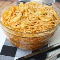 Spaghetti salad in a glass bowl on a black plaid placemat