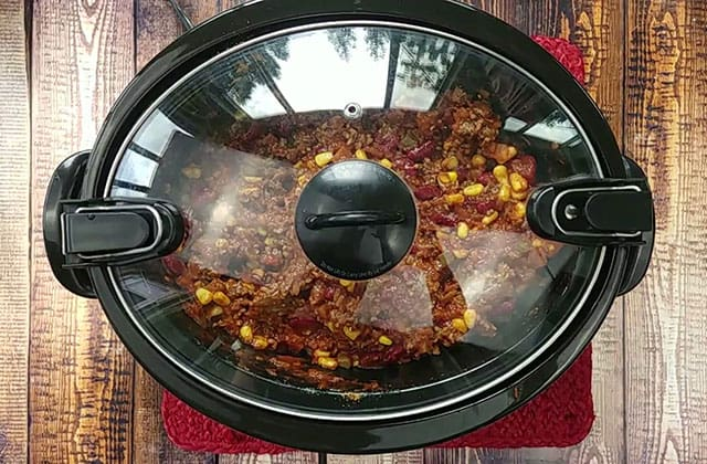 Chili cooking in a black crockpot with a glass lid