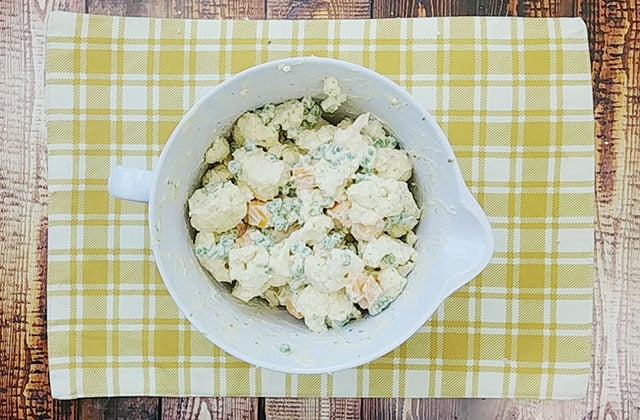 Prepared cauliflower salad in a white mixing bowl on a plaid placemat