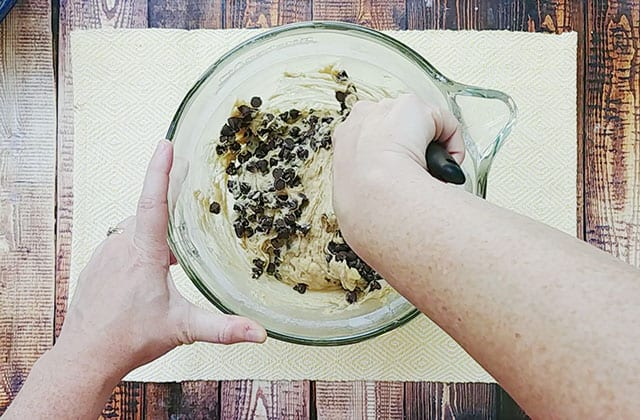 Stirring chocolate chips into the cookie dough in a glass mixing bowl