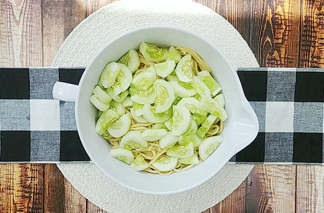 Cooked spaghetti and cucumbers in a large white mixing bowl