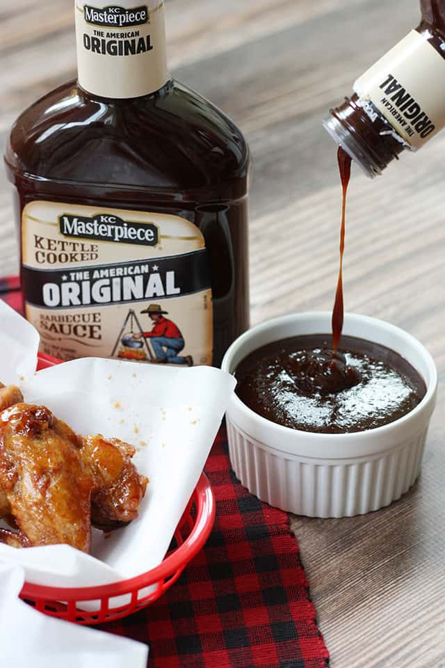 Pouring bbq sauce into a white ramekin next to a basket of bbq wings