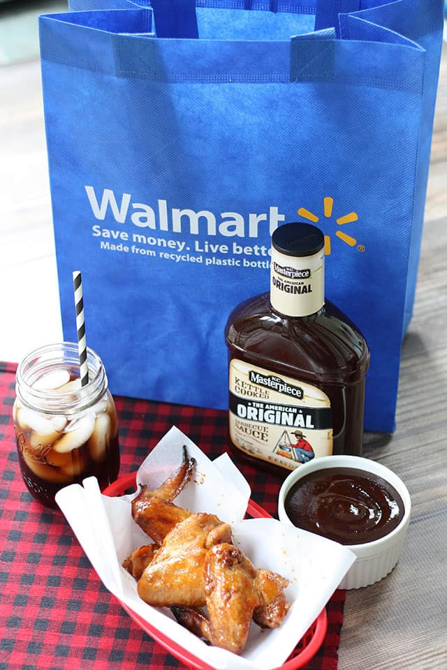 Chicken wings and a bottle of bbq sauce in front of a Walmart reusable shopping bag