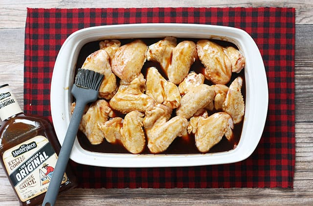 Chicken wings in a baking dish with glazed poured over them and a basting brush