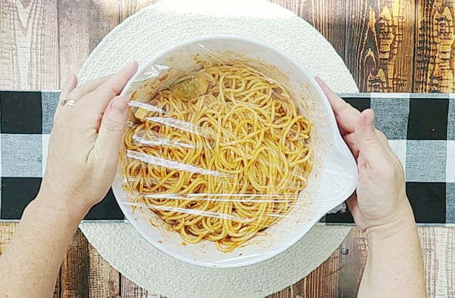 Cover spaghetti salad in a white bowl with plastic cling wrap