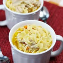 White soup mugs filled with chicken noodle soup on a red placemat