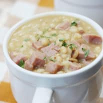 A close up picture of navy bean soup in a white soup mug