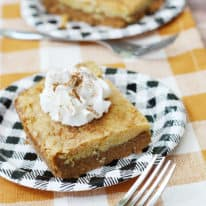 Slices of pumpkin dump cake on black plaid paper plates