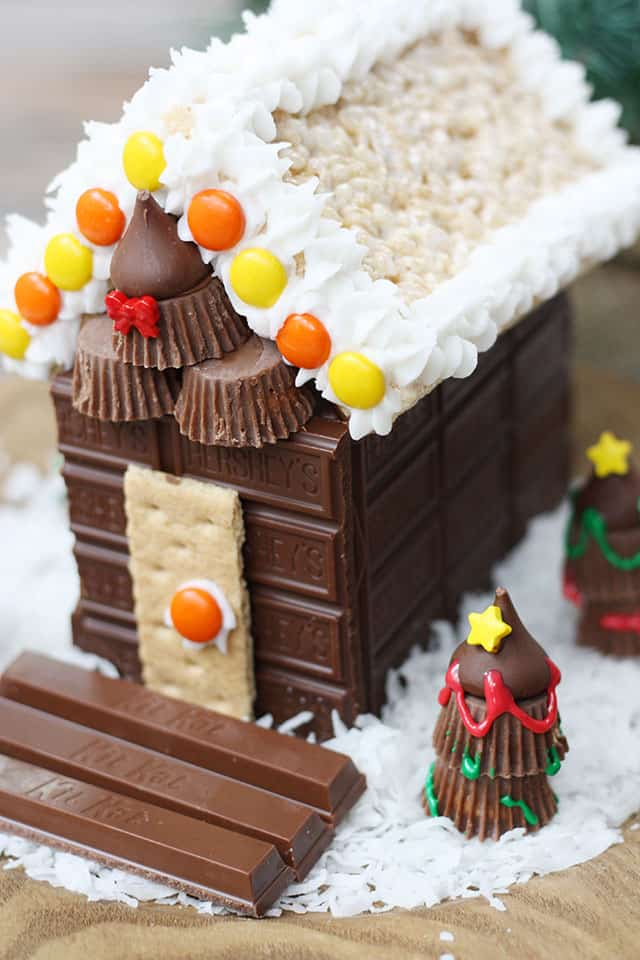 Christmas Candy Cabin centerpiece on a wooden charger
