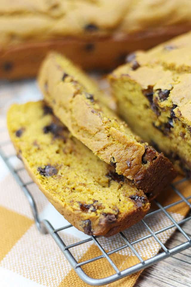 Slices of chocolate chip pumpkin bread on a wire rack on an orange plaid napkin