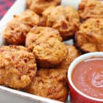 Pizza muffins in a dish next to some marinara sauce for dipping