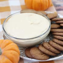 Pumpkin dip in a glass bowl with ginger snaps next to it