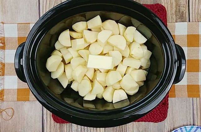 Peeled and chopped potatoes and butter in a Crockpot
